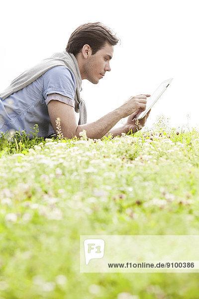 liegend  liegen  liegt  liegendes  liegender  liegende  daliegen  durchsichtig  transparent  transparente  transparentes  benutzen  Mann  Himmel  Ansicht  jung  Tablet PC  Seitenansicht  Gras