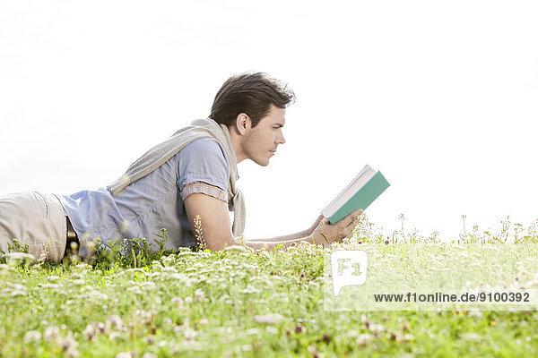 liegend  liegen  liegt  liegendes  liegender  liegende  daliegen  durchsichtig  transparent  transparente  transparentes  Mann  Buch  Himmel  Ansicht  jung  Seitenansicht  Gras  Taschenbuch  vorlesen