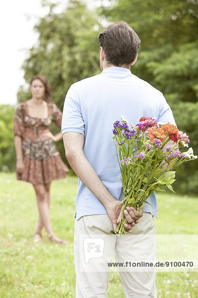 Rear view man surprising woman with flowers in park