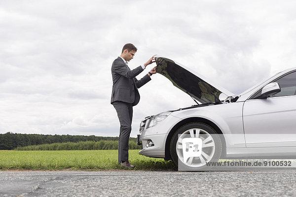 aufmachen  Geschäftsmann  Ländliches Motiv  ländliche Motive  Auto  Ansicht  jung  Motorhaube  Länge  Seitenansicht  zerbrochen  voll  Kapuze