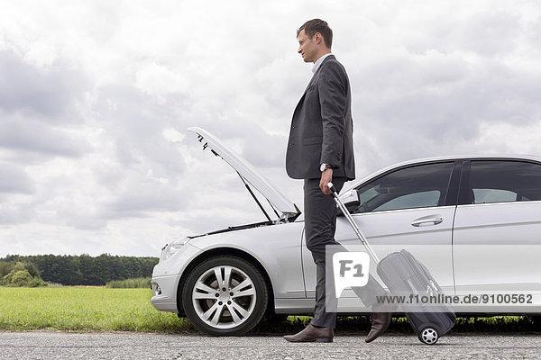Geschäftsmann  Ländliches Motiv  ländliche Motive  gehen  Auto  Gepäck  Ansicht  jung  Länge  Seitenansicht  zerbrochen  voll