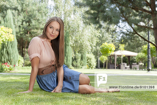 Full length of beautiful young woman looking away while relaxing on grass in park