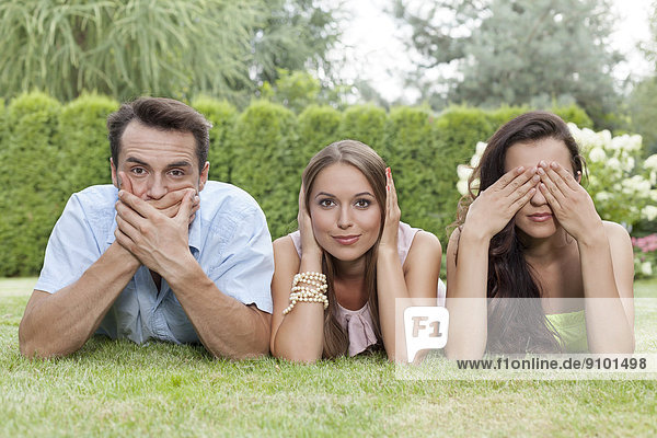 Portrait of young friends covering mouth  ears and eyes in park