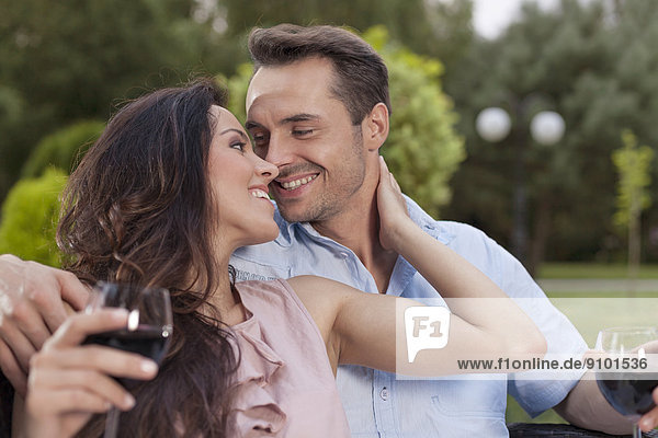 Romantic young couple with wine glasses in park