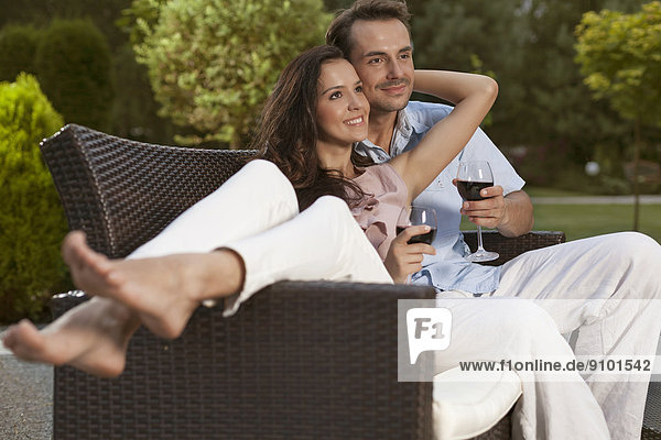 Romantic young couple on easy chair looking away in park