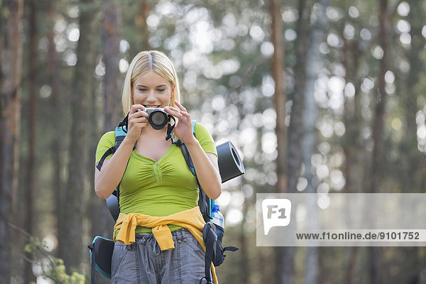Female hiker photographing through digital camera in forest