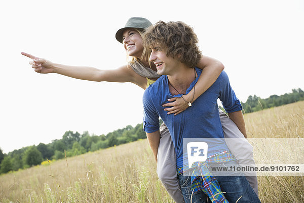 zeigen  Frau  Mann  Fröhlichkeit  fahren  Feld  huckepack  mitfahren