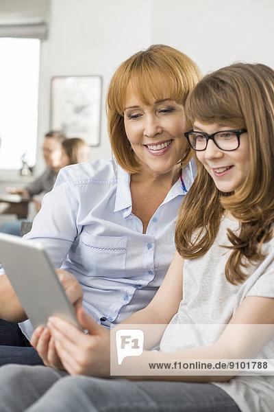 sitzend  Interior  zu Hause  benutzen  Computer  Fröhlichkeit  Hintergrund  Tochter  Mutter - Mensch  Tablet PC