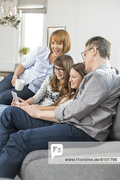 Cheerful family using tablet PC on sofa at home