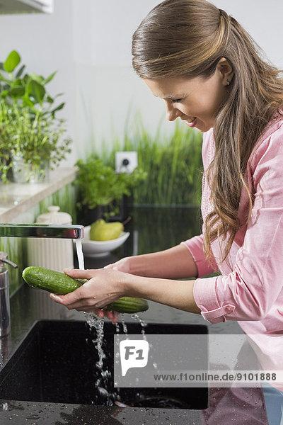 Frau  lächeln  waschen  Küche  Gurke