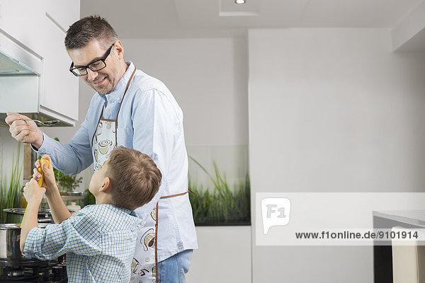 Happy father and son preparing spaghetti in kitchen