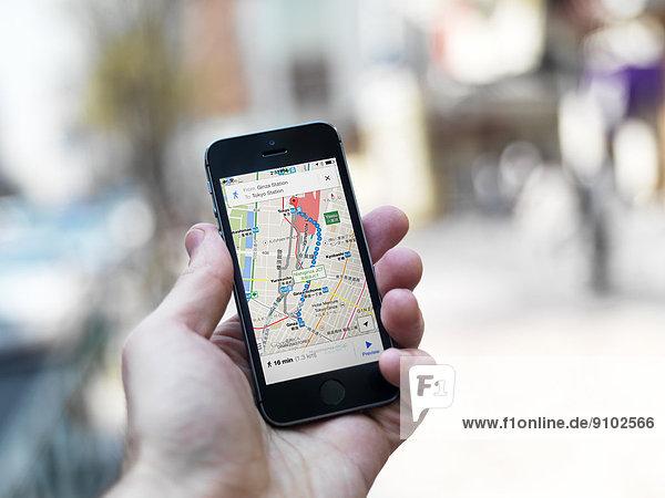 Eine Hand hält ein iPhone mit Google Maps auf dem Display  GPS-Navigator mit den Straßen von Tokio  Tokio  Japan