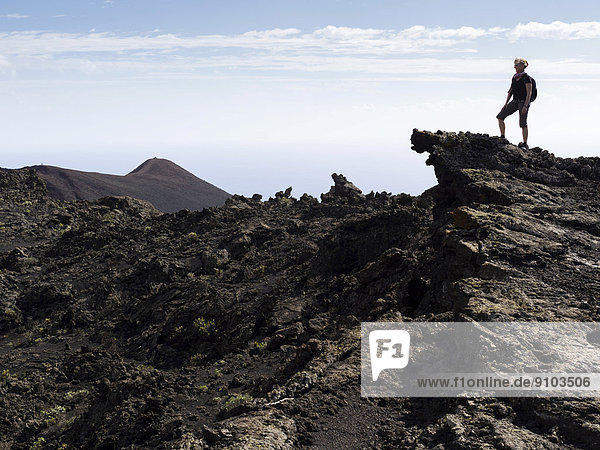 A hiker standing on a rock in the volcanic landscape  San Antonio volcano and Teneguia volcano at the back  Los Canarios  Fuencaliente  La Palma  Canary Islands  Spain