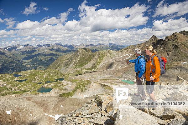 Zwei Wanderer auf dem Pass Fuorcla da Barcli  unten die Macun-Seen  Schweizerischer Nationalpark  Graubünden  Schweiz