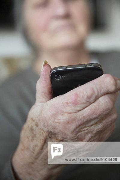 Seniorin hält ein Smartphone
