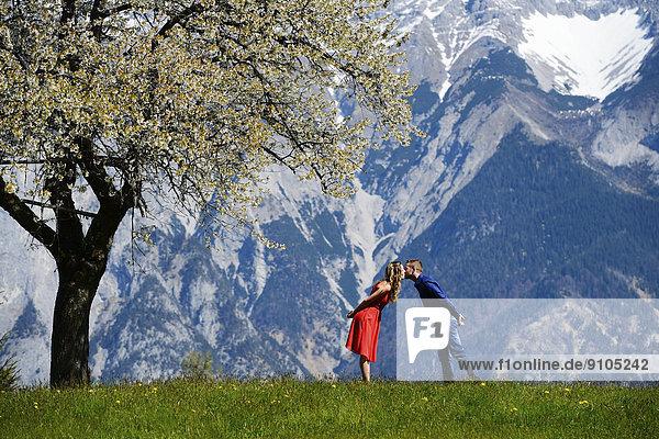 Liebespaar küsst sich neben einem blühenden Baum im Frühling  hinten Berge  Tirol  Österreich