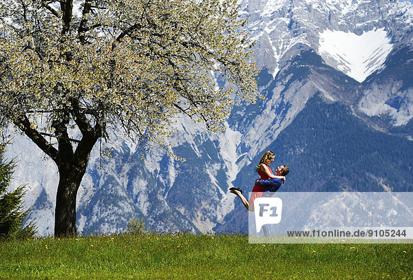 Liebespaar umarmt sich neben einem blühenden Baum im Frühling  hinten Berge  Tirol  Österreich Liebespaar umarmt sich neben einem blühenden Baum im Frühling, hinten Berge, Tirol, Österreich
