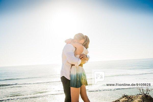 Romantisches junges Paar umarmt sich an der Küste