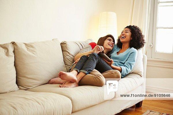 Junges weibliches Paar auf dem Sofa liegend mit Blick auf das digitale Tablett