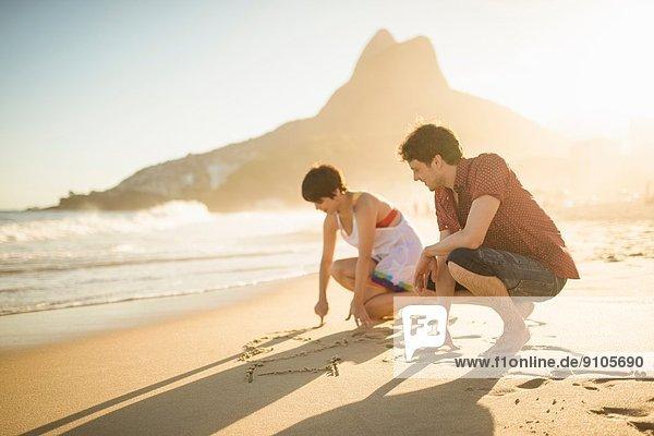 Young couple writing on sand  Ipanema Beach  Rio  Brazil