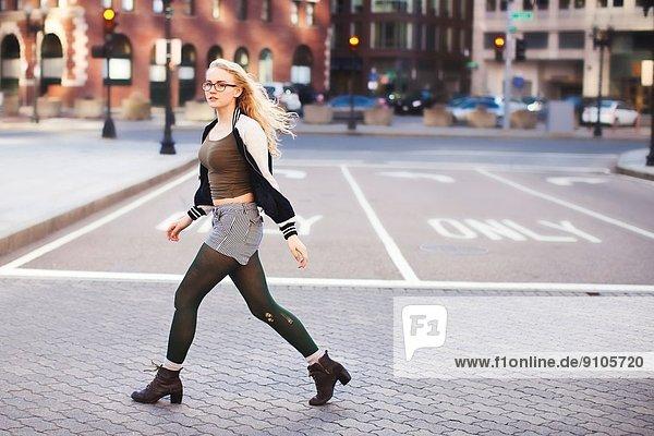 Junge Frau geht die Straße entlang