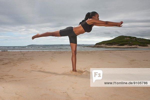 Junge Frau beim Yoga auf einem Bein am Strand