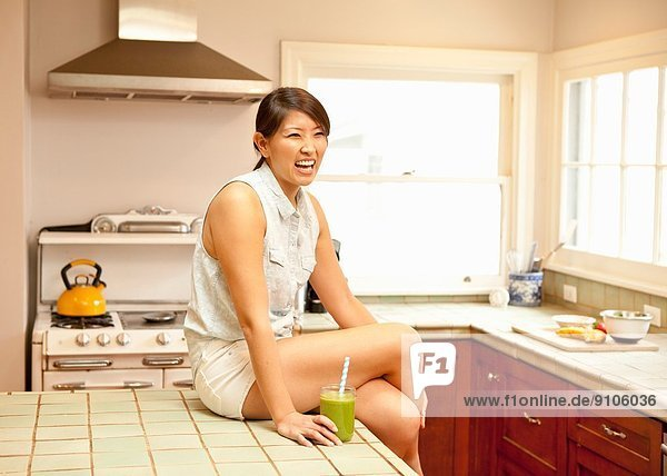 Young woman with green smoothie in kitchen