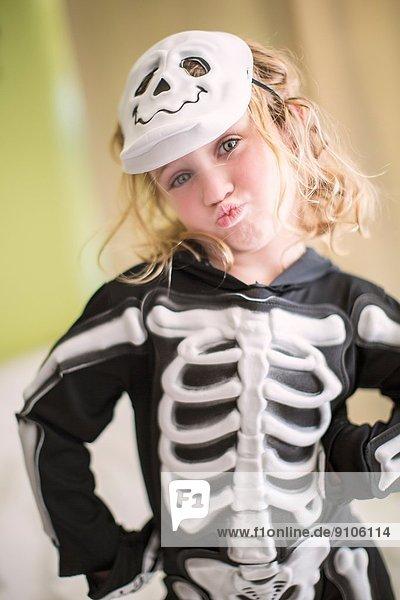Portrait eines jungen Mädchens in Skelettkostüm mit Totenkopfmaske