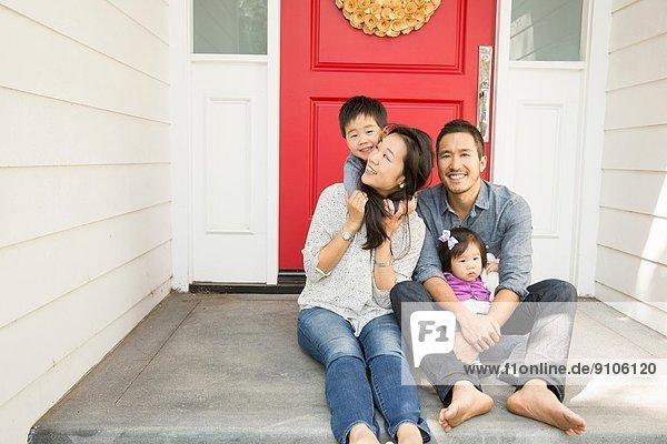 Porträt eines mittleren erwachsenen Paares mit jungem Sohn und Tochter auf der Veranda