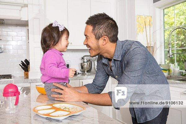 Mittelgroßer Mann mit Kleinkind-Tochter auf Küchenarbeitsplatte