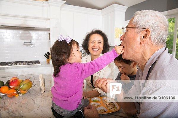 Weibliches Kleinkind füttert den Großvater in der Küche