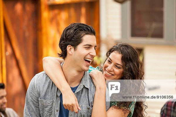 Ehepaar im Garten  mit dem Arm um den Arm  Freunde im Hintergrund