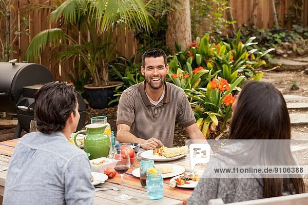 Friends sitting around table sharing barbecue food