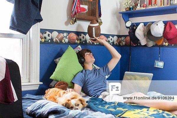 Teenager Junge auf dem Bett liegend mit Laptop  Fußball und Hund