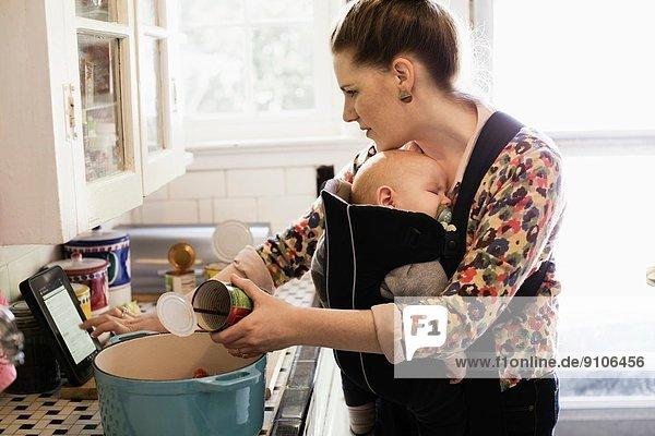 Mittlere erwachsene Mutter mit Babysohn im Tragetuch beim Zubereiten von Speisen in der Küche