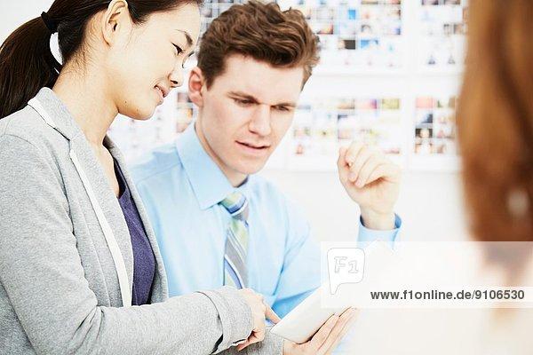 Geschäftskollegen im Gespräch mit digitalem Tablett
