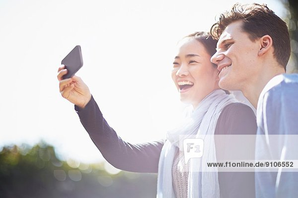 Junges Paar fotografiert sich mit dem Smartphone