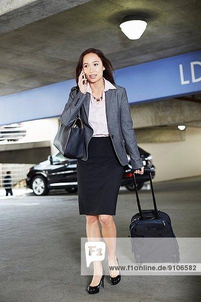 Junge Geschäftsfrau mit Rollkoffer auf dem Parkplatz