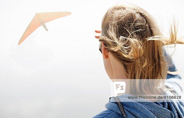 Frau beobachtet Drachenflieger am Himmel