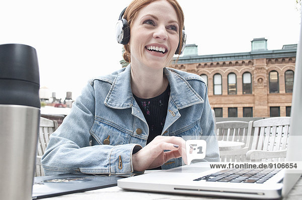 Young woman using laptop and headphones on rooftop