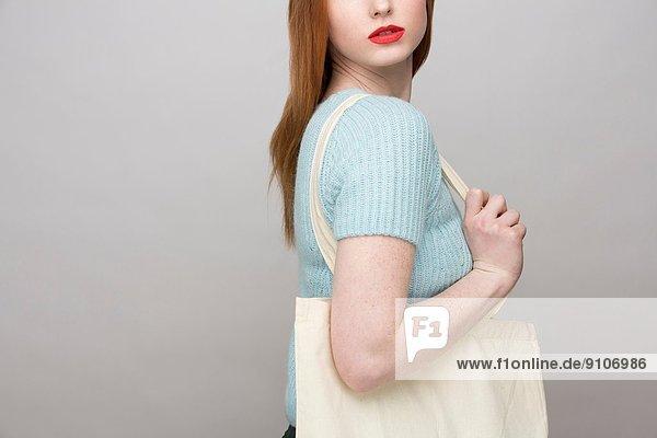 Abgeschnittenes Bild einer jungen Frau mit Einkaufstasche