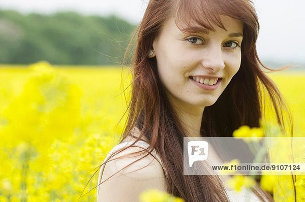 Portrait of young woman in yellow field