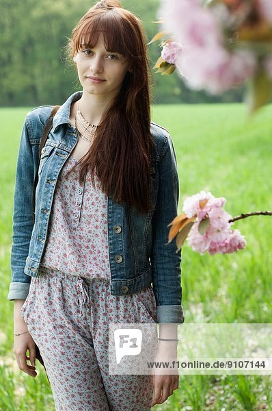 Portrait of serious young woman in field