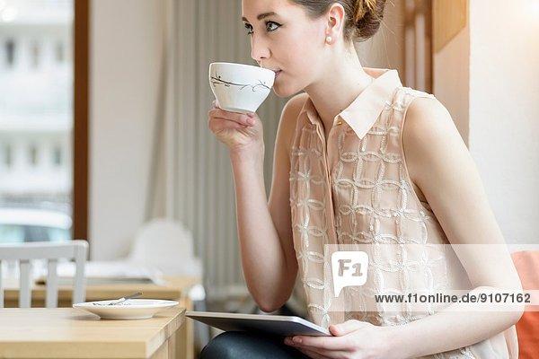 Junge Geschäftsfrau im Café  die Kaffee trinkt und digitale Tabletten benutzt