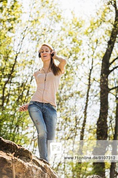 Junge Frau hört Musik und balanciert auf dem Rock