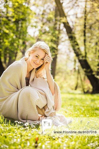Porträt einer jungen Frau im Wald in Decke gehüllt