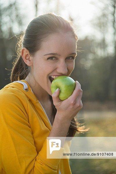 Porträt einer jungen Läuferin beim Apfelessen