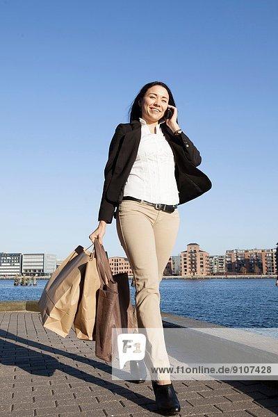 Geschäftsfrau beim Gehen mit Smartphone  Kopenhagen  Dänemark