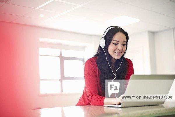 Junge Frau mit Kopfhörer am Laptop