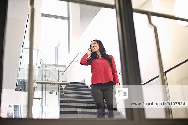 Junge Frau auf der Treppe mit dem Handy